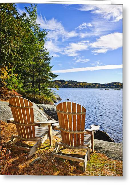 Deck Chairs Greeting Cards - Adirondack chairs at lake shore Greeting Card by Elena Elisseeva