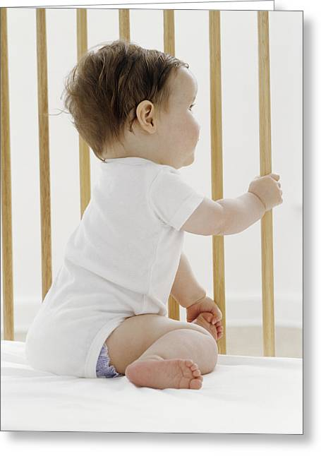 Child Care Greeting Cards - Baby Girl In A Cot Greeting Card by Ian Boddy