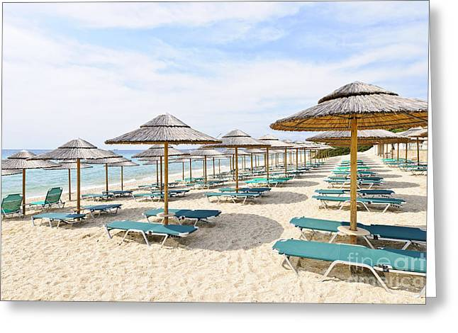 Shade Greeting Cards - Beach umbrellas on sandy seashore Greeting Card by Elena Elisseeva