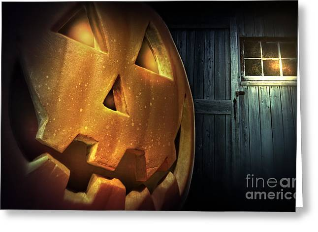 Old Barns Greeting Cards - Glowing pumpkin at night in front of barn door Greeting Card by Sandra Cunningham