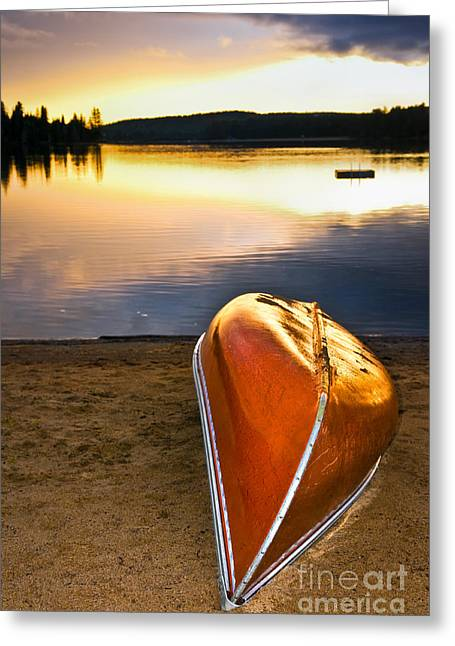 Algonquin Greeting Cards - Lake sunset with canoe on beach Greeting Card by Elena Elisseeva