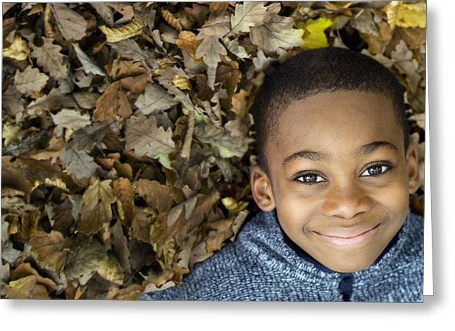 Child Care Greeting Cards - Smiling Boy Lying On Autumn Leaves Greeting Card by Ian Boddy