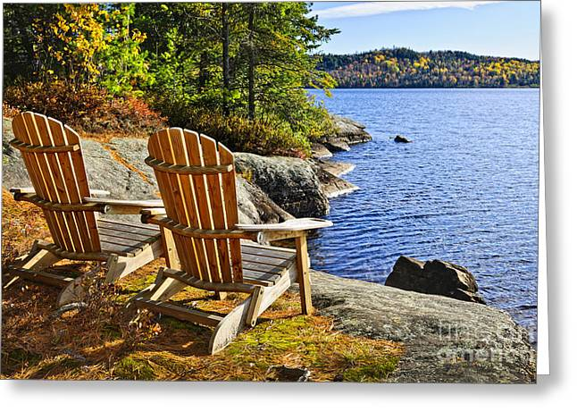Beautiful Scenery Greeting Cards - Adirondack chairs at lake shore Greeting Card by Elena Elisseeva
