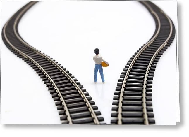 Considering Greeting Cards - Figurine between two tracks leading into different directions symbolic image for making decisions. Greeting Card by Bernard Jaubert