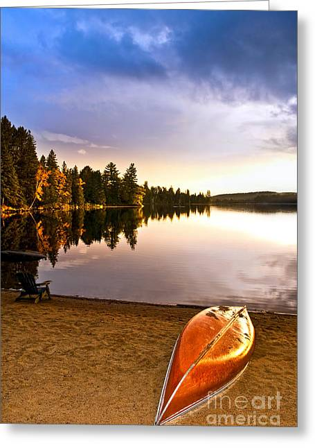 Beach Landscape Greeting Cards - Lake sunset with canoe on beach Greeting Card by Elena Elisseeva
