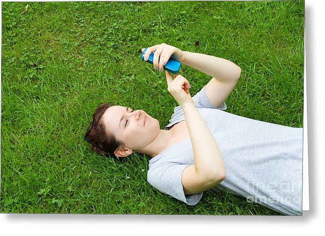 Woman Using Her Iphone Greeting Card by Photo Researchers, Inc.