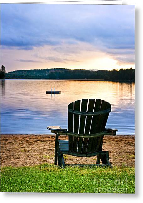 Beach Landscape Greeting Cards - Wooden chair at sunset on beach Greeting Card by Elena Elisseeva