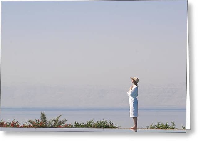 A Woman Enjoys The Warm Sun On The Edge Greeting Card by Taylor S. Kennedy