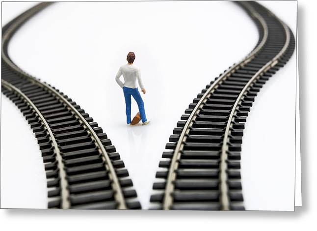 Choosing Photographs Greeting Cards - Figurine between two tracks leading into different directions symbolic image for making decisions. Greeting Card by Bernard Jaubert