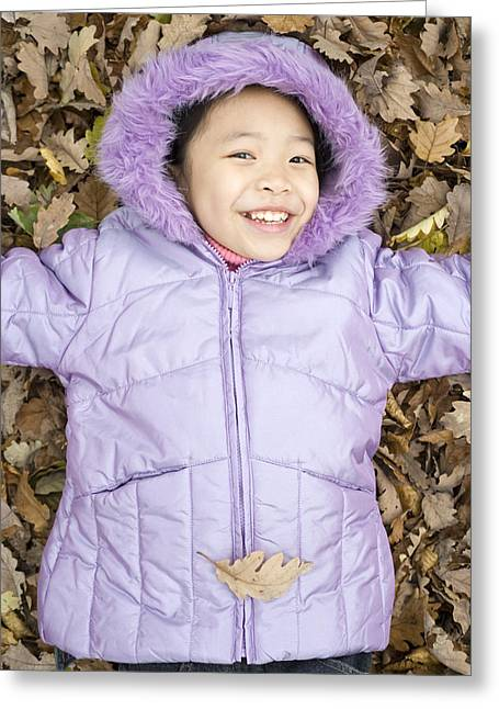 Child Care Greeting Cards - Smiling Girl Lying On Autumn Leaves Greeting Card by Ian Boddy