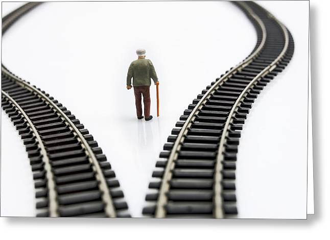 Stick Greeting Cards - Figurine between two tracks leading into different directions symbolic image for making decisions. Greeting Card by Bernard Jaubert