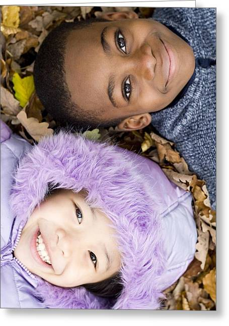 Child Care Greeting Cards - Smiling Children Lying On Autumn Leaves Greeting Card by Ian Boddy