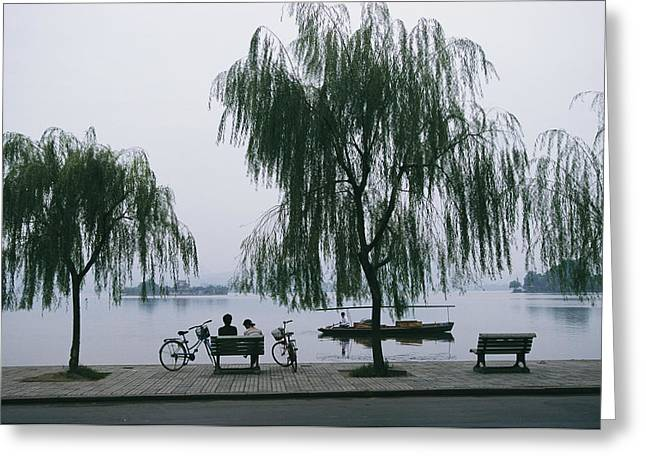 Willow Lake Greeting Cards - A Boat Passes By Bicyclists On A Bench Greeting Card by James L. Stanfield