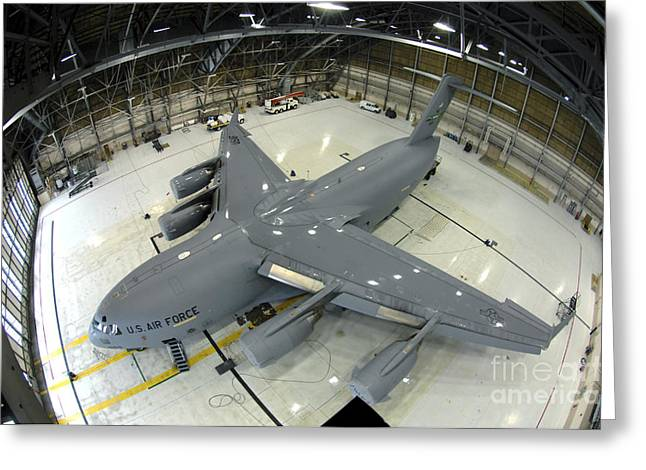 Freight Aircraft Greeting Cards - A C-17 Globemaster Iii Sits In Hangar 4 Greeting Card by Stocktrek Images