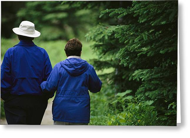 Couple In Arms Greeting Cards - A Couple Stroll Down A Path In Yoho Greeting Card by Michael Melford