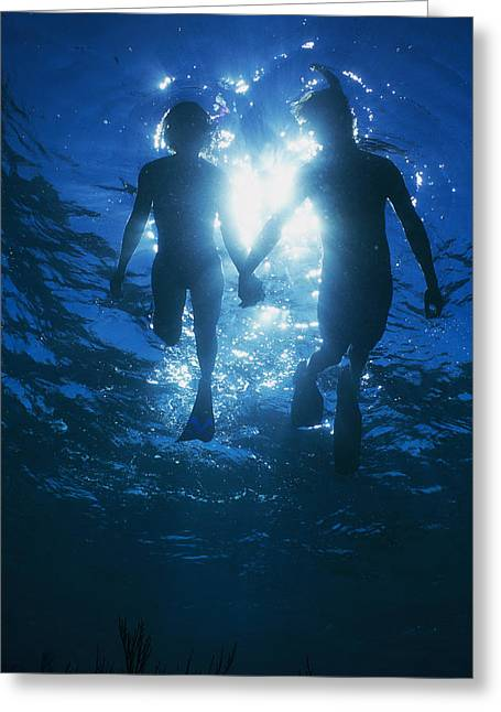 By Humans Greeting Cards - A Couple Swimming Hand-n-hand Greeting Card by Nick Caloyianis