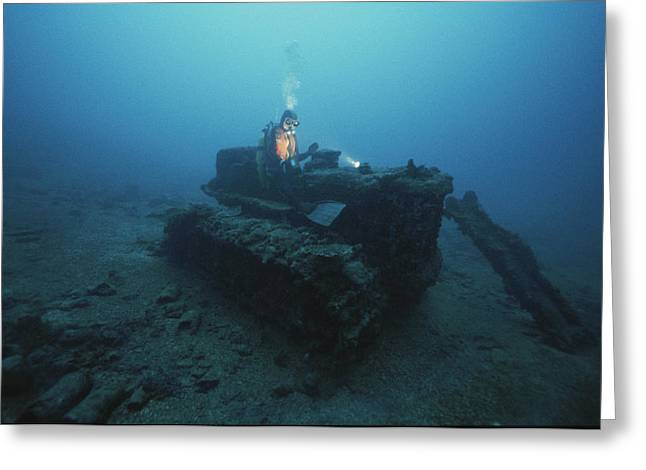 A Diver Inspects A Tractor Dumped Greeting Card by David Doubilet
