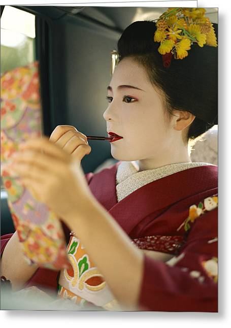 Kansai Photographs Greeting Cards - A Kimono-clad Geisha Applies Lipstick Greeting Card by Justin Guariglia