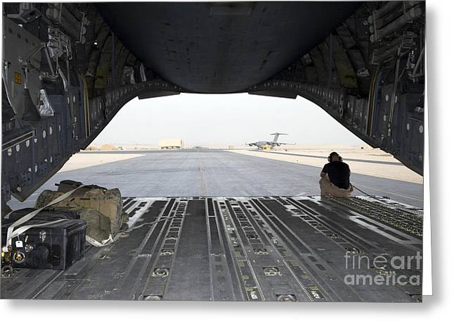 Airfield Greeting Cards - A Loadmaster Sits On The Rear Ramp Greeting Card by Terry Moore
