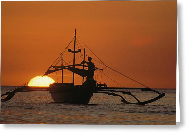 Sunset Scenes. Greeting Cards - A Man And An Outrigger Silhouetted Greeting Card by Paul Chesley