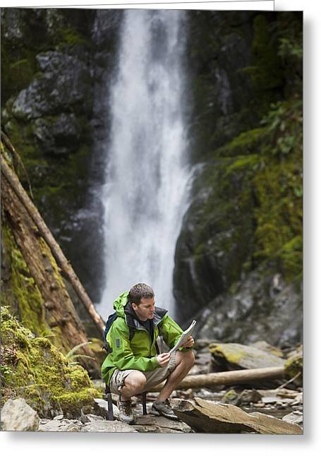 Serene People Greeting Cards - A Man Looks At A Map In The Wilderness Greeting Card by Taylor S. Kennedy