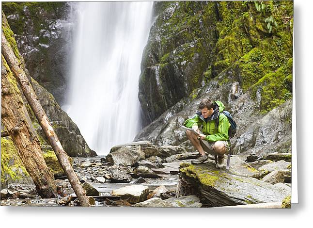 Moss Green Greeting Cards - A Man Looks At A Map While Crouched Greeting Card by Taylor S. Kennedy