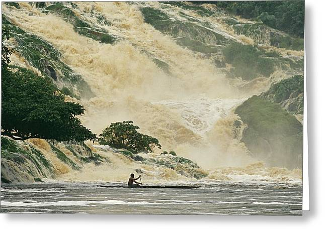 Canoe Waterfall Greeting Cards - A Man On A Canoe Near The Crashing Greeting Card by Michael Nichols
