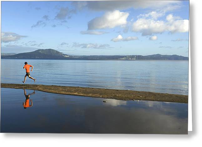 Jogging Greeting Cards - A Man Running On A Beach Is Reflected Greeting Card by Bill Hatcher