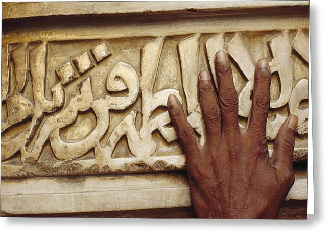 Art Of Building Greeting Cards - A Man Runs His Hand Over Arabic Script Greeting Card by Justin Guariglia