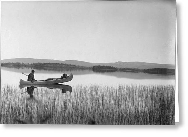 Willow Lake Greeting Cards - A Man Sits In A Canoe On The Tranquil Greeting Card by George Shiras