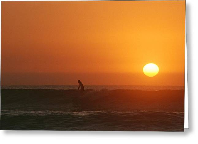 Surf Silhouette Greeting Cards - A Man Surfs As The Sun Sets Greeting Card by Jimmy Chin