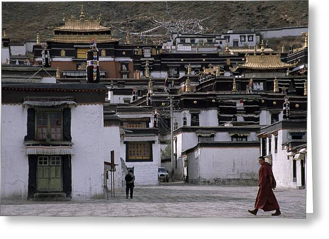 Chang Greeting Cards - A Monk Walks Past A Small Village Greeting Card by Jimmy Chin