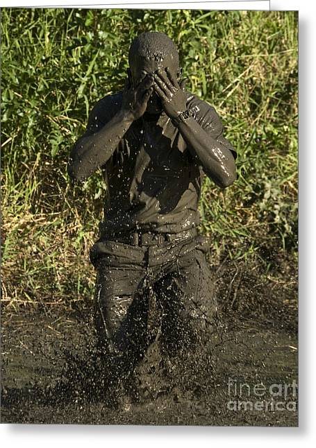 Physical Fitness Greeting Cards - A Participant Wipes Mud From His Face Greeting Card by Stocktrek Images