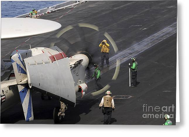 Cvn-69 Greeting Cards - A Sailor Directs An E-2c Hawkeye Greeting Card by Stocktrek Images