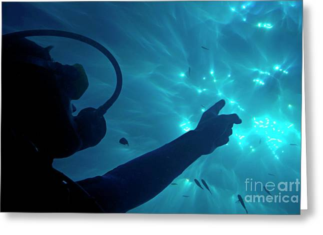 Scuba Diving Greeting Cards - A scuba diver pointing the sunbeams penetrating the water Greeting Card by Sami Sarkis