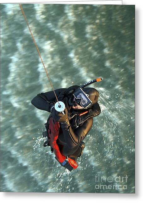 Swimmers Greeting Cards - A Search And Rescue Swimmer Is Hoisted Greeting Card by Stocktrek Images