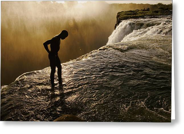 Zambia Waterfall Greeting Cards - A Swimmer Stands At The Lip Of A Hidden Greeting Card by Annie Griffiths
