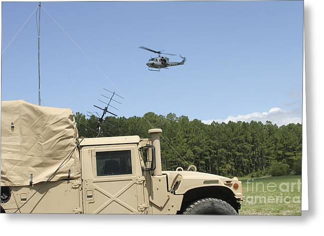 Hmmwv Greeting Cards - A Uh-1n Helicopter Flies Greeting Card by Stocktrek Images