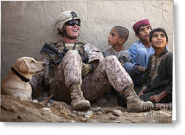 Helmand Province Greeting Cards - A U.s. Marine Jokes With Afghan Greeting Card by Stocktrek Images