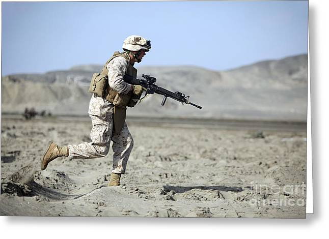 Assault Weapons Greeting Cards - A U.s. Marines Runs Across The Beach Greeting Card by Stocktrek Images