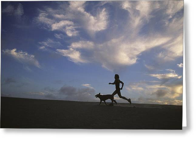 Jogging Greeting Cards - A Woman And Her Dog Run Along The Beach Greeting Card by Skip Brown