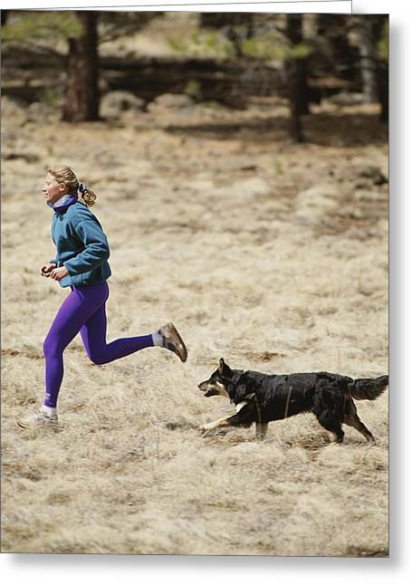 Jogging Greeting Cards - A Woman And Her Dog Running In A Grassy Greeting Card by Dugald Bremner Studio