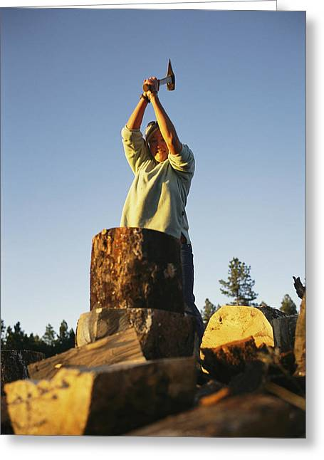 Mid Adult Women Greeting Cards - A woman chops wood with Greeting Card by Bobby Model