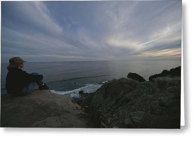 Looking Out Side Greeting Cards - A Woman In A Hat Sits On Cliff Looking Greeting Card by Todd Gipstein