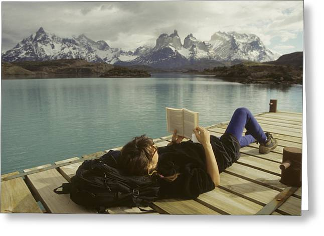 Mid Adult Women Greeting Cards - A Woman Relaxes On A Dock While Reading Greeting Card by Skip Brown