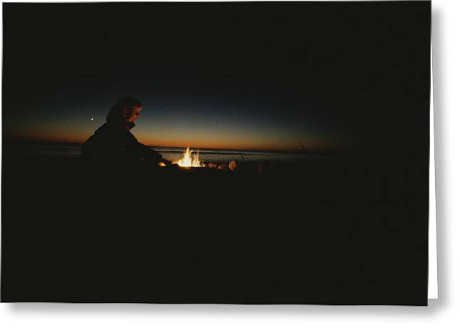 Mid Adult Women Greeting Cards - A Woman Tends A Fire On A Beach Greeting Card by Todd Gipstein