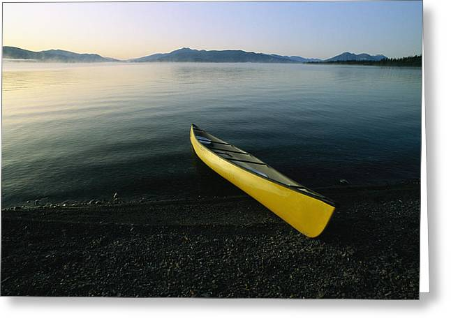 Canoe Photographs Greeting Cards - A Yellow Canoe On The Shore Of A Calm Greeting Card by Michael Melford