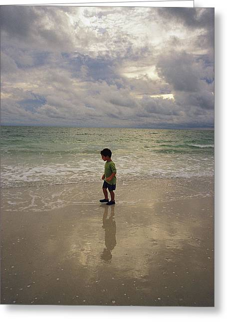 Alejandro Greeting Cards - A Young Boy Walks Along A Beach Greeting Card by Raul Touzon