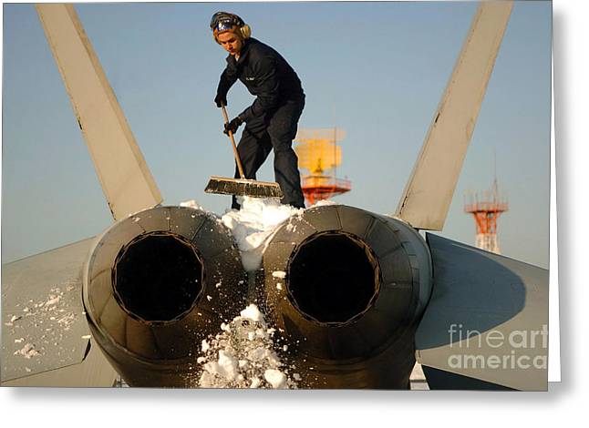 F-18 Greeting Cards - Airman Scrapes Snow Off The Tail Of An Greeting Card by Stocktrek Images
