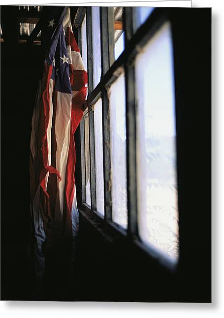Window Of Life Greeting Cards - An American Flag Hangs In A Window Greeting Card by Raul Touzon